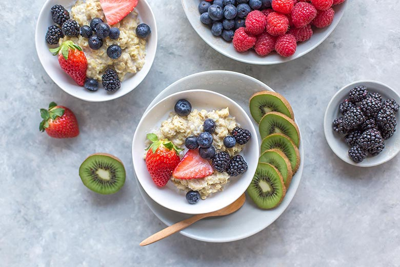 Oatmeal with berries and kiwi fruit in bowls
