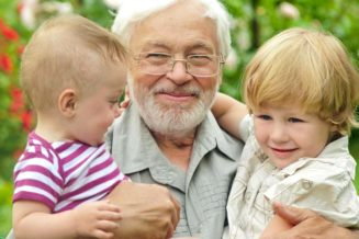 Grandfather holding young grandchildren