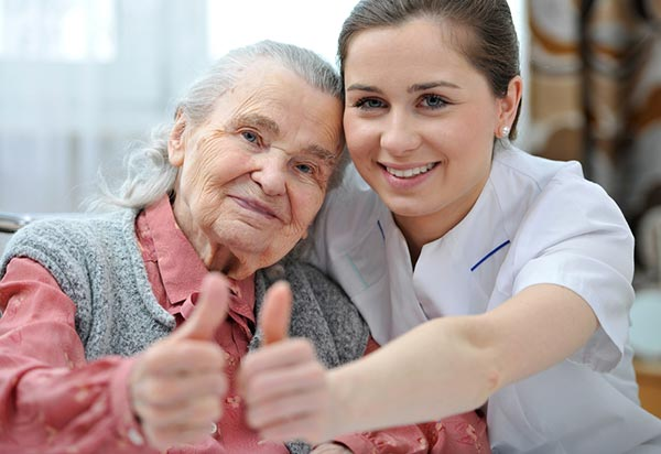 Caregiver with senior woman with thumbs up