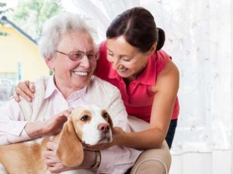 Senior woman with her dog and home caregiver