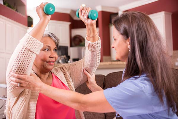 Caregiver helping senior woman with weight lifting program