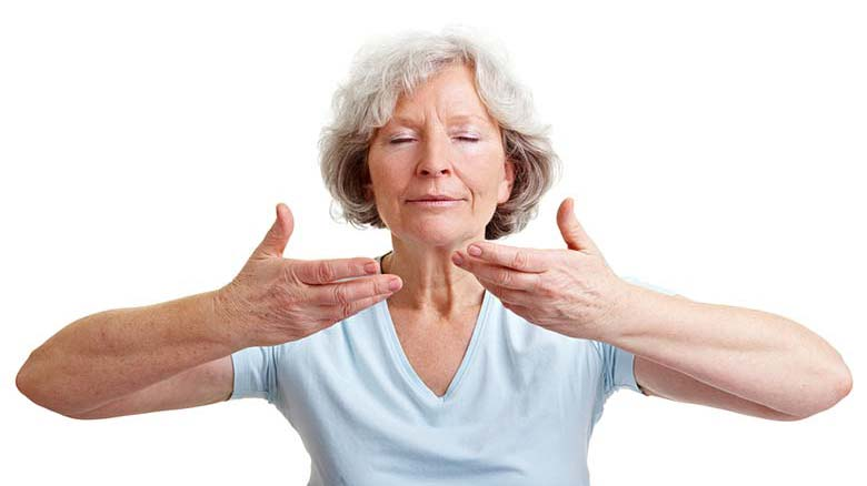 Senior woman stretching and breathing with eyes closed