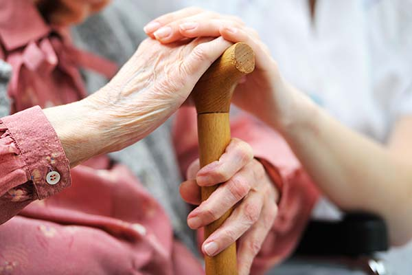 Senior woman holding cane with caregiver