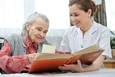 caregiver with elderly woman reading book
