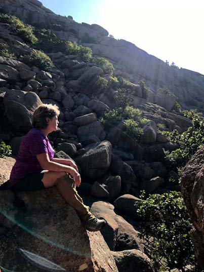 Sue Henderson sitting on a rock with sunshine and mountain