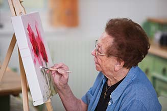 Elderly woman painting flowers on a canvas
