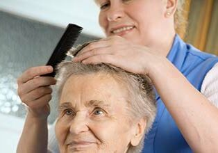 Caregiver combing hair for senior