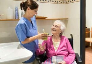 Caregiver helping smiling senior woman brush her teeth