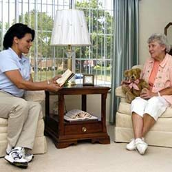 Caregiver reading to senior woman in home
