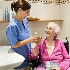 Caregiver helping senior woman with grooming