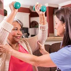 Caregiver helping senior woman work out